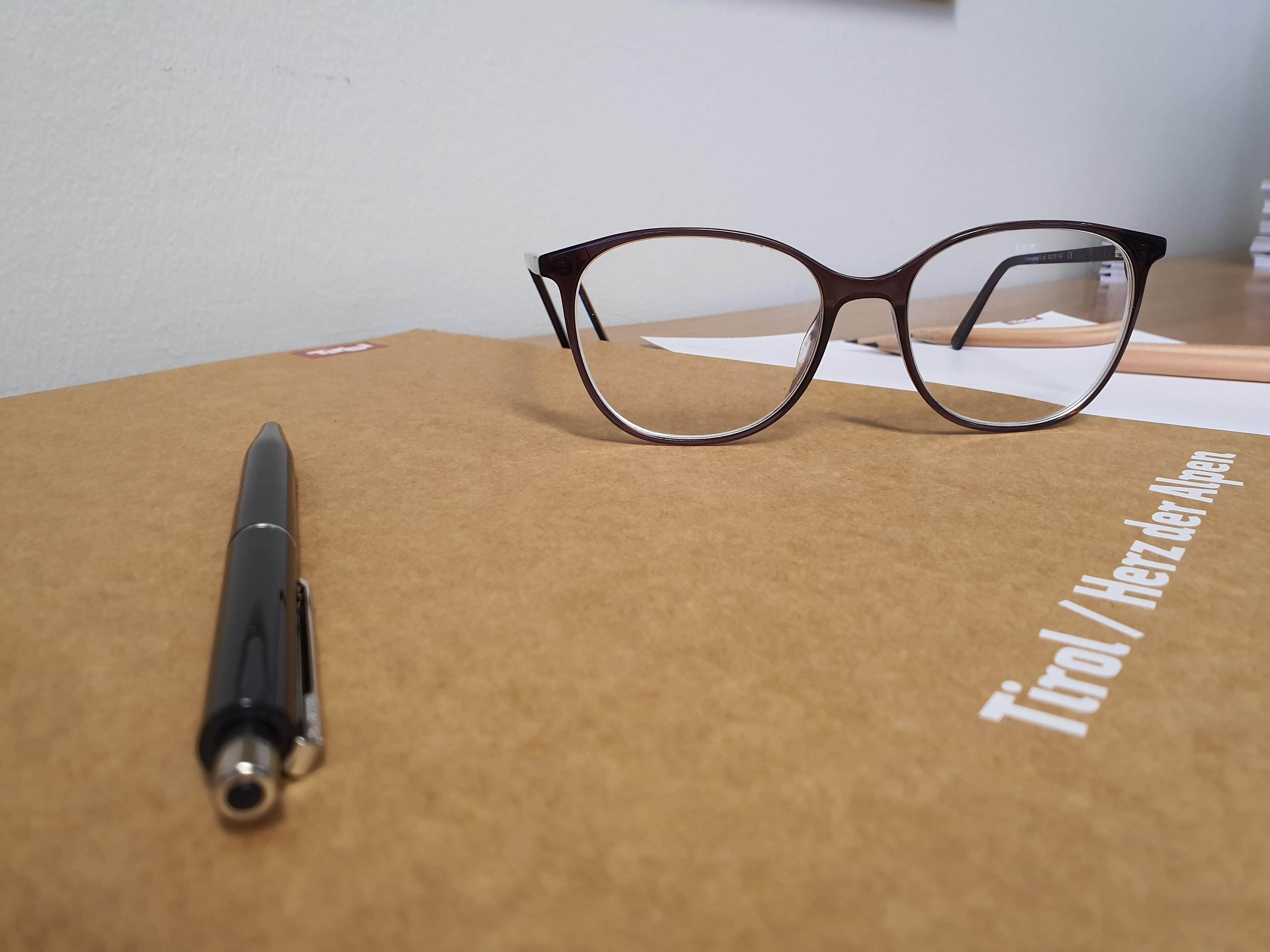 Stift, Mappe und Brille