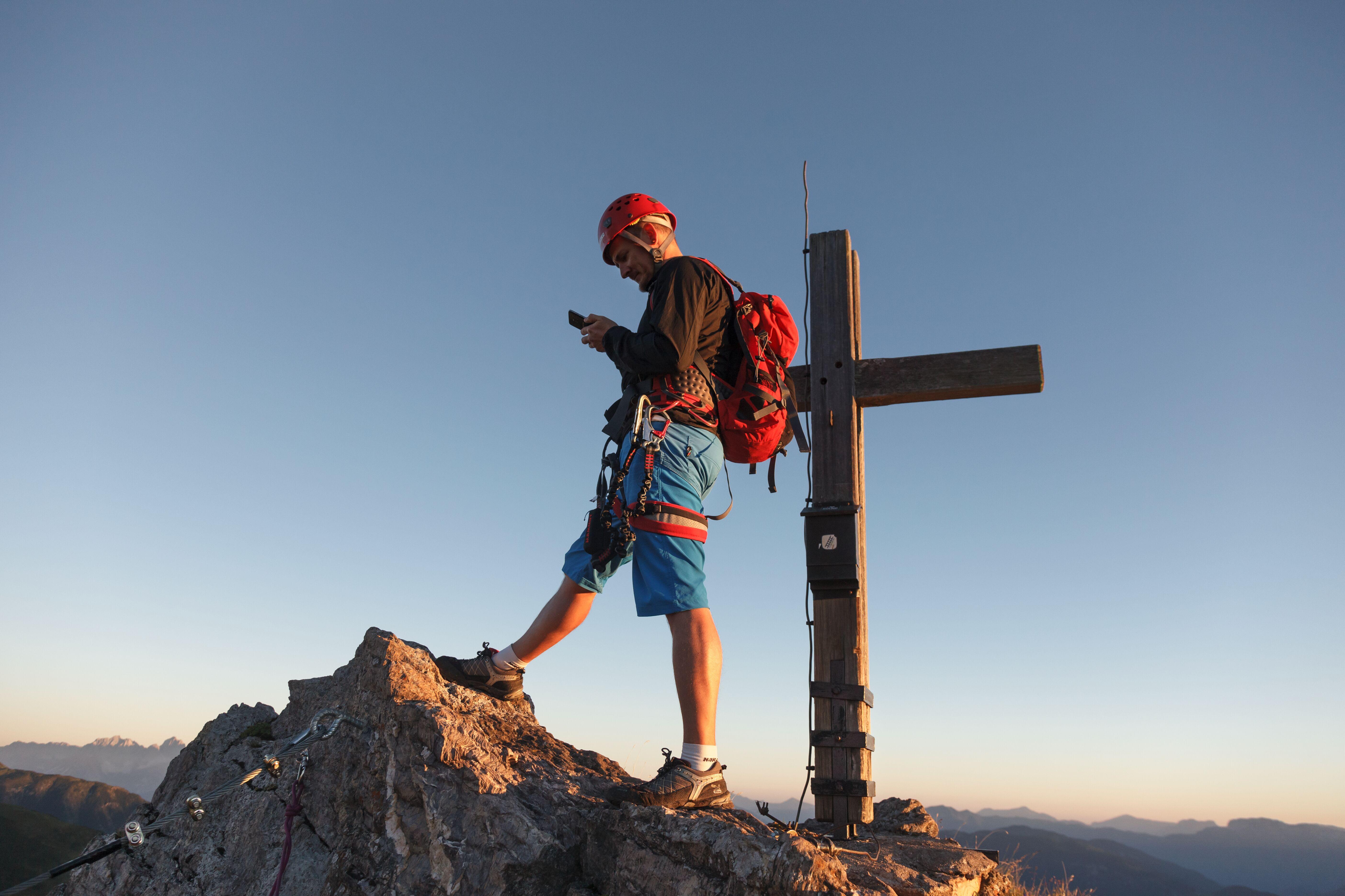 Bergsteiger mit Handy vor Gipfelkreuz