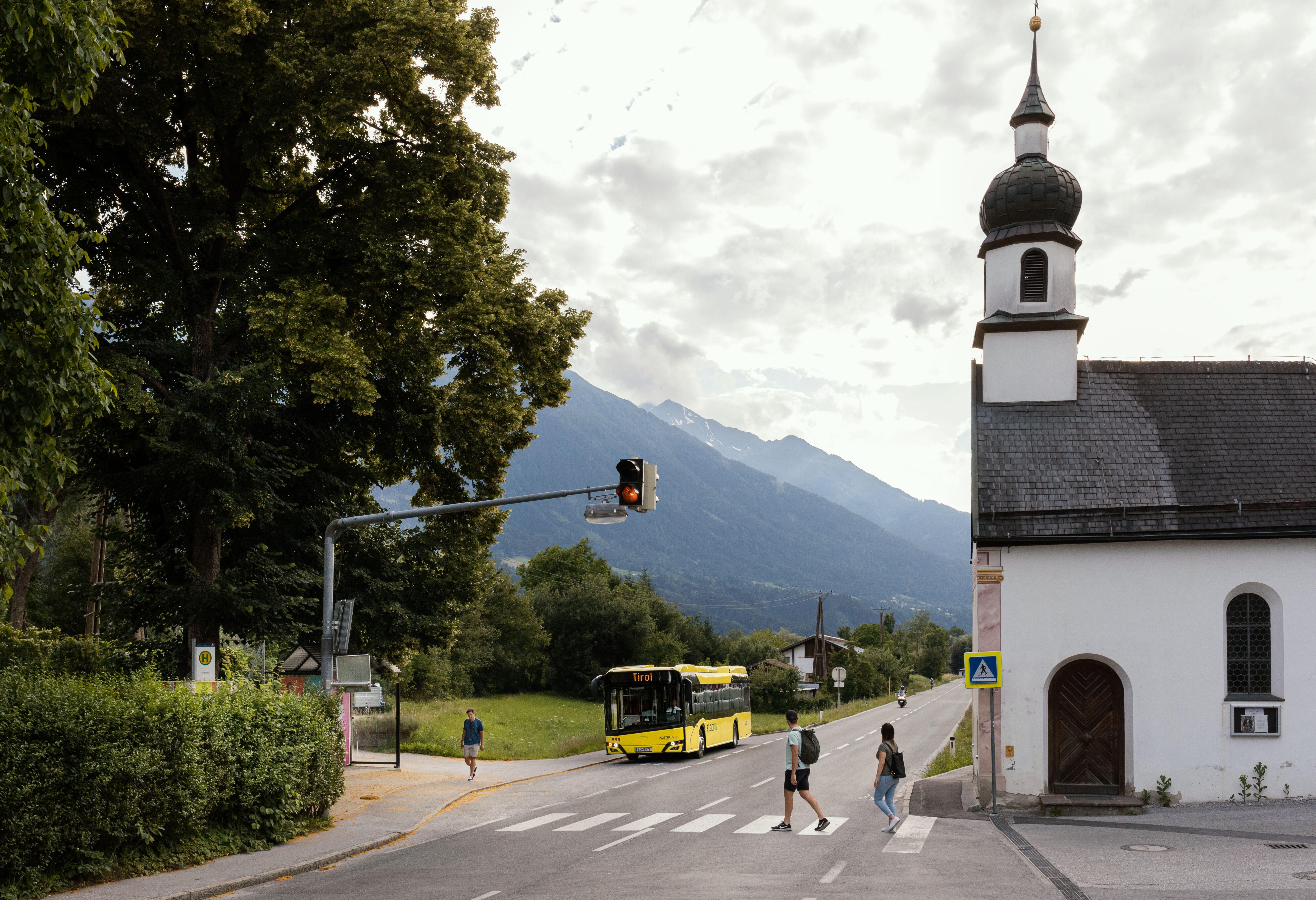 Bus in Eigenhofen, Menschen überqueren Zebrastreifen